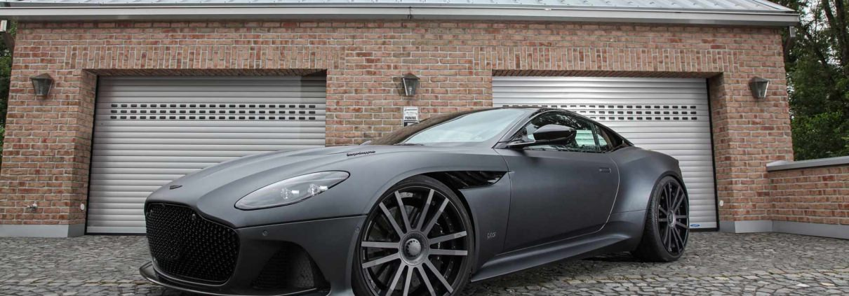 front side view aston martin dbs superleggera in front of garage wearing 22 inch wheels from wheelsandmore tuning